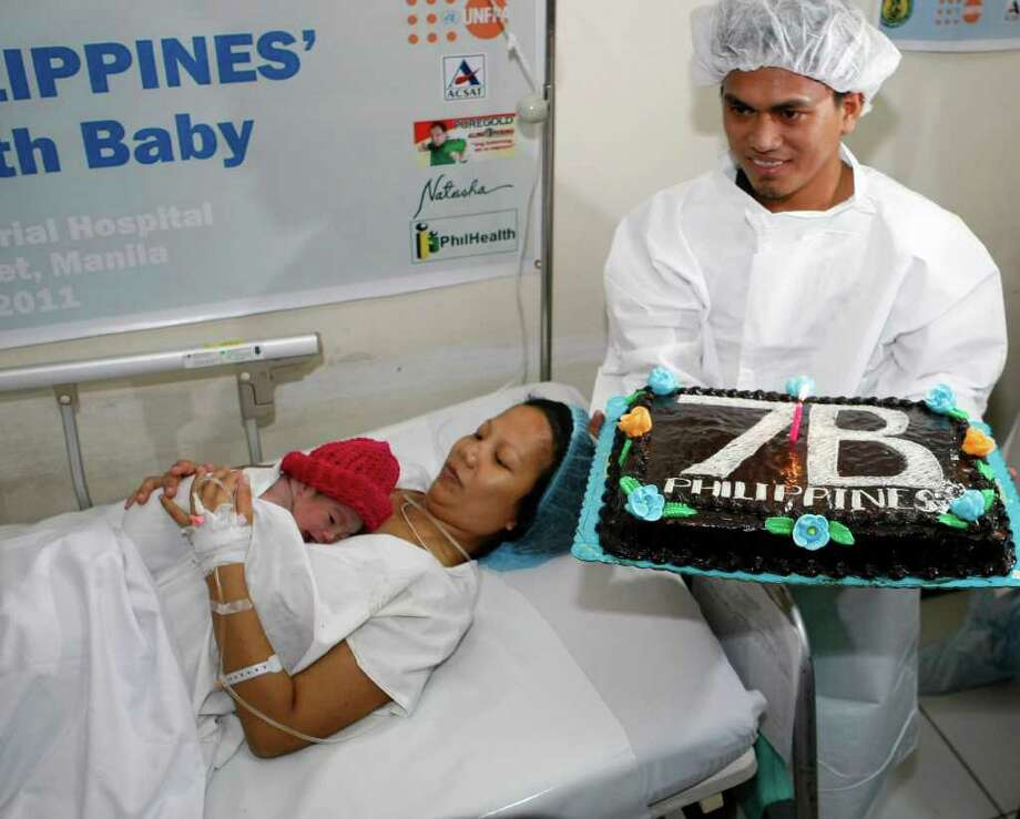 Danica Camacho is cuddled by her mother Camille as her father Florante Galura holds a cake shortly after she was born at the Government's Fabella Hospital Monday Oct.31, 2011 in Manila, Philippines. The Philippines, ranked 12th as the most populated country in the world, joins the rest of the world as it welcomes its symbolic 7 billionth baby in simple ceremony in Manila. (AP Photo/Bullit Marquez) Photo: BULLIT MARQUEZ, Associated Press / AP