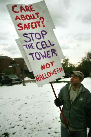 Phil Simpson of Trumbull protests the proposed cell tower outside police headquarters on Edison Road in Trumbull on Monday, October 31, 2011. Simpson's sign refers to the fact that First Selectman Timothy Herbst asked residents not to trick or treat on Halloween for safety reasons. Photo: Brian A. Pounds / Connecticut Post