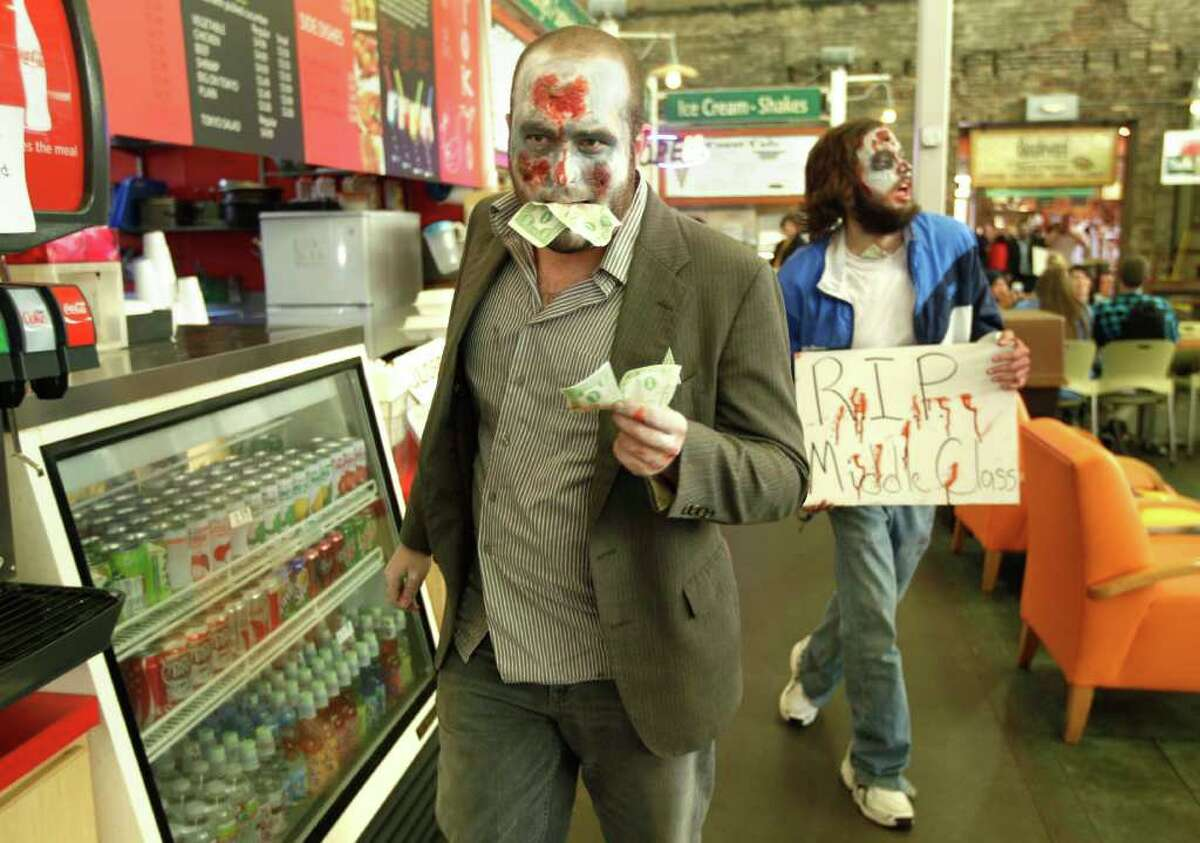 Occupy Wall Street protesters, made up to look like zombies for Halloween, pretend to eat money as they walk through a dining area at the River Market district in Little Rock, Ark., Monday, Oct.31, 2011.