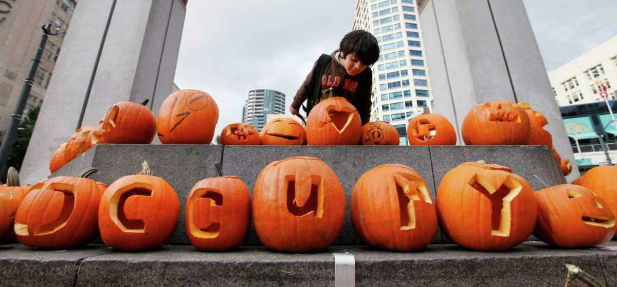 Rick Navarro, 6, looks over carved pumpkins, some spelling out