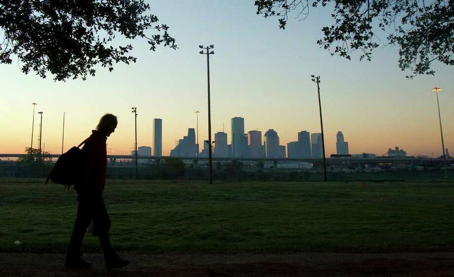 "Gary Taylor walks through Stude Park Tuesday, Nov. 1, 2011, in Houston. ""I love it,"" Taylor said. ""When you're camped out in warm weather like this, it's like an air conditioning."" (Cody Duty / Houston Chronicle) Photo: Cody Duty / © 2011 Houston Chronicle"