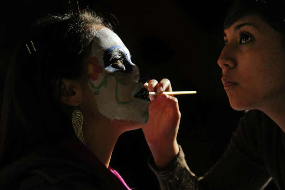 Jimena Jimenes-Aguilar sits for Ariana Arreola at the Dia de los Muertos celebration held by the Latin American Student Organization on Thursday, Oct. 27, 20011 at California Lutheran University in Thousand Oaks, Calif. Photo: AP
