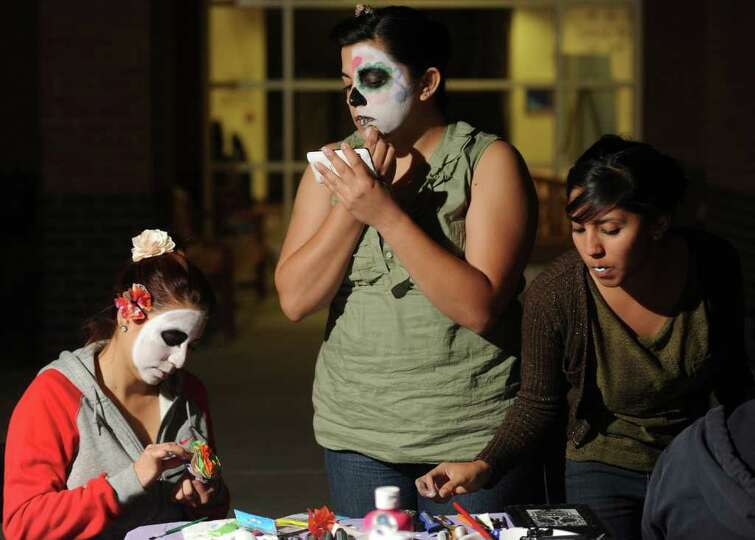Erika Salazar, 23, uses her cell phone as a mirror to do her makeup at the Dia de los Muertos celebr