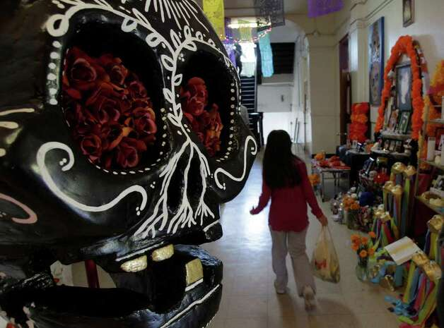 A child passes through the altar exhibit during the annual festival Dia De Los Muertos at  MECA, 1900 Kane,  Saturday, Oct. 29, 2011, in Houston.  Dia de los Muertos or Day of the Dead is a traditional Latin American holiday that honors and celebrates the lives of family and friends who died. Traditionally held November 1 and 2,  the belief is that the dead return home, visit loved ones, and feast on their favorite foods.  The festival continues Sunday, October, 30 from 11 am to 6 pm.  The event features an altar exhibit,  foods, arts and crafts, music and dance performances, and a children's area with art and game activities. Photo: Melissa Phillip, Houston Chronicle / © 2011 Houston Chronicle