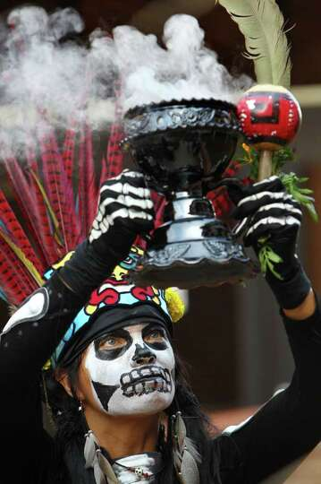Maricela Rodriguez-Lou holds up a sahumador, an incense burner, as the group Quetzalcoatl begins the