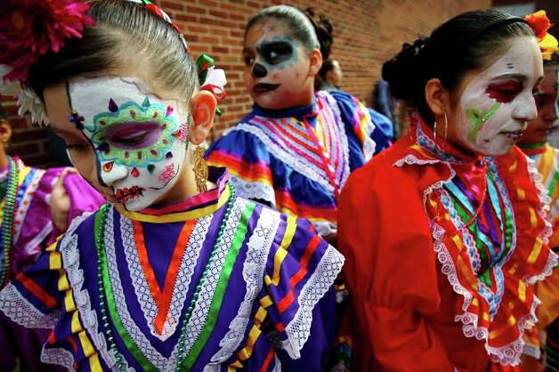 Mayralin Ponce, 11, Joanna Santos, 10 and Stephany Sandoval, 13, stand around together after performing a dance during a Dia de los Muertos celebration at the University of Memphis, Sunday, Oct. 30, 2011, in Memphis, Tenn. Photo: AP
