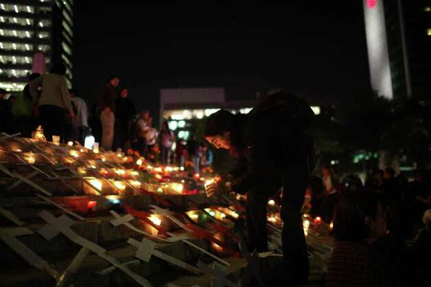 A man lights candles during a protest against violence during Day of the Dead celebrations in Mexico City, Monday, Oct. 31, 2011.  Mexico's drug war has claimed over 35,000 lives nationwide since President Felipe Calderon intensified the crackdown on the cartels in December 2006. Photo: AP
