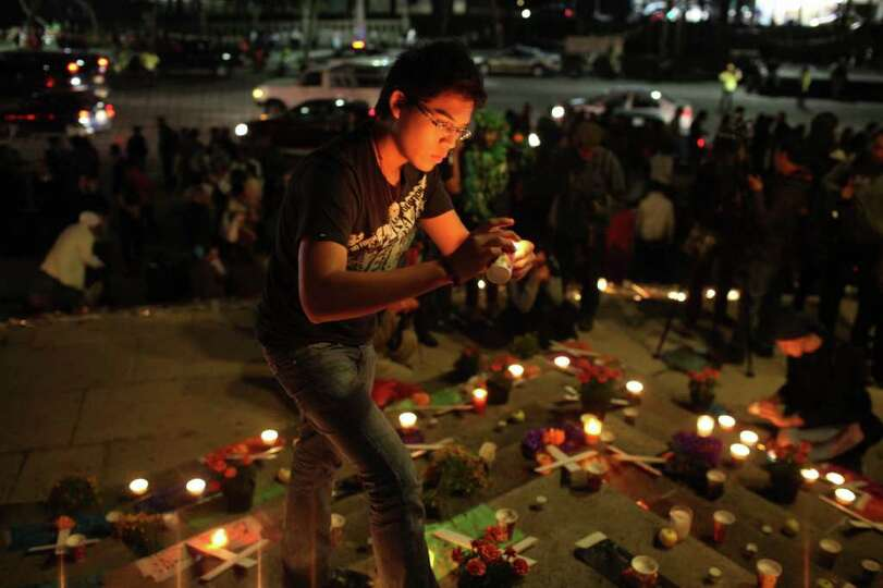 A man lights candles during a protest against violence during Day of the Dead celebrations in Mexico