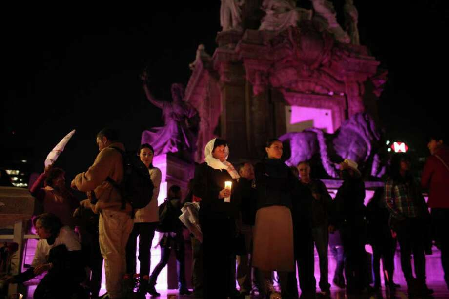 People gather during a protest against violence as part of the Day of the Dead celebrations at the Angel of Independence monument Mexico City, Monday, Oct. 31, 2011.  Photo: AP