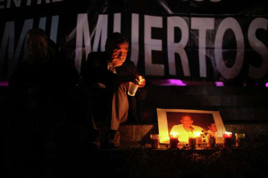 A man lights candles during a protest against violence during Day of the Dead celebrations in Mexico City, Monday, Oct. 31, 2011.  Photo: AP