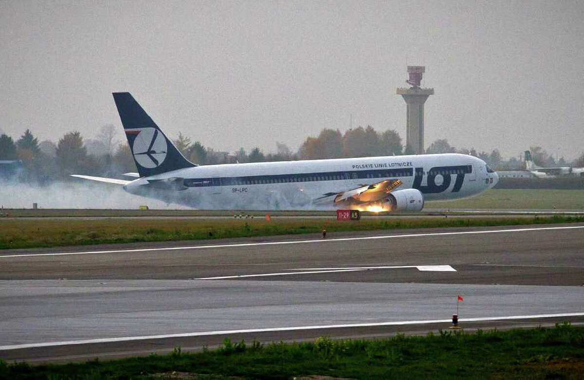 A LOT Polish airlines Boeing 767 flying from New York with 227 people on board makes an emergency landing at Warsaw's airport on Tuesday, Nov. 1, 2011 after having problems lowering its landing gear. The plane had dropped fuel and circled above Warsaw for some time and a landing strip was especially prepared at the airport for the crash landing. No one was injured during the emergency landing according to a LOT spokesman. AFP PHOTO / WOJTEK RADWANSKI