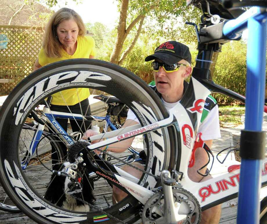 DAVID HOPPER: FOR THE CHRONICLE READY TO ROLL: Jody Schoger watches her husband, Steve, work on his bicycle at their home in The Woodlands. Both are members of The Woodlands Cycling Club. Photo: David Hopper / freelance