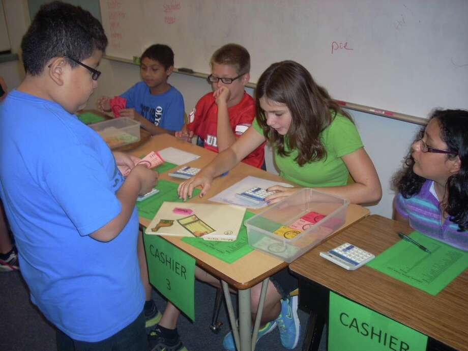 "Olympia Elementary fifth-grade ""cashier"" Jordan Shelley counts the ""Unicorn cash"" of customer Adrian Viera. Shelley's fellow cashiers are Tommy Ho (seated far left), Adam Duncan and Alize Martinez (far right). Photo: Photo Courtesy Of Aubrey Chancellor/Judson ISD"