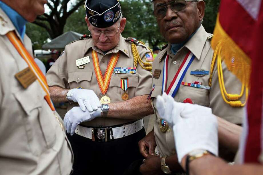 """THOSE WHO SERVED: Buddy Blair, center, puts on his gloves as John B. Jackson right, looks on as the Texas Lone Star Korean War Veterans prepare to present the colors before the annual """"Houston Salutes American Heroes Veterans Day Commemoration and Parade"""" Nov. 11, 2010. Photo: Eric Kayne / Freelance"""