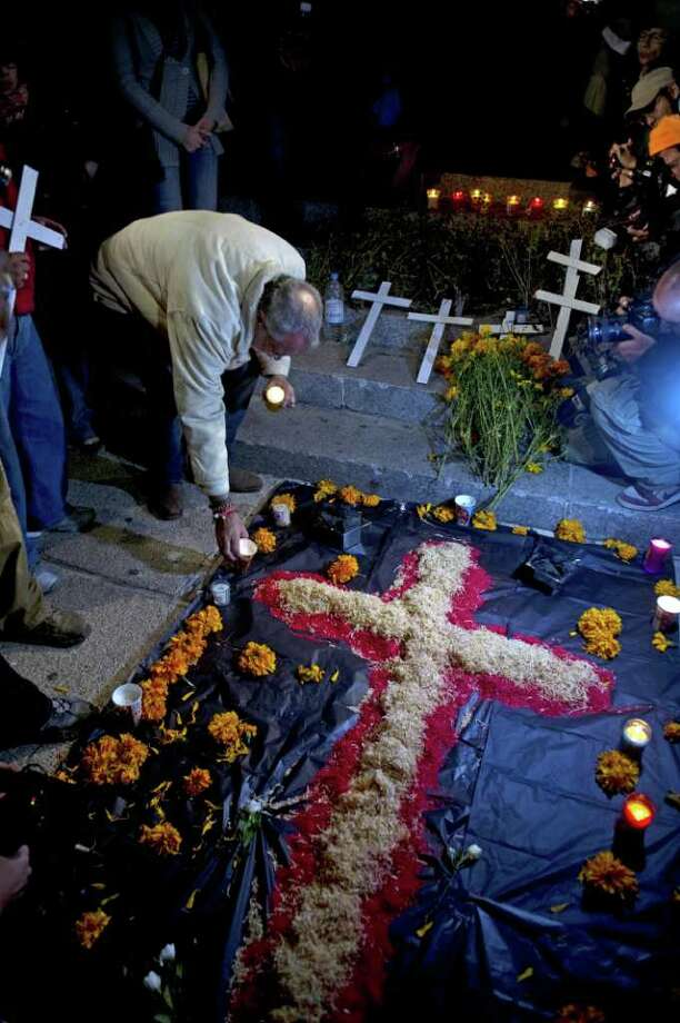 "The leader of Movement for Peace with Justice and Dignity, Mexican poet Javier Sicilia places a candle in an altar in memory of more than forty thousands victims of violence at the ""Angel Square"" in Mexico City on October 31, 2011. Photo: YURI CORTEZ, AFP/Getty Images / 2011 AFP"