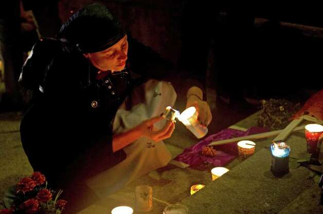 "A woman member of Movement for Peace with Justice and Dignity leaded by Mexican poet Javier Sicilia lights candles in an altar in memory of more than forty thousands victims of violence at the ""Angel Square"" in Mexico City on October 31, 2011.  Thousands of people ramain in twenty four hours of vigil to demand a stop of the violence and remember their loved ones on the eve of ""The Day of the Dead.""   AFP PHOTO/Yuri CORTEZ Photo: YURI CORTEZ, AFP/Getty Images / 2011 AFP"