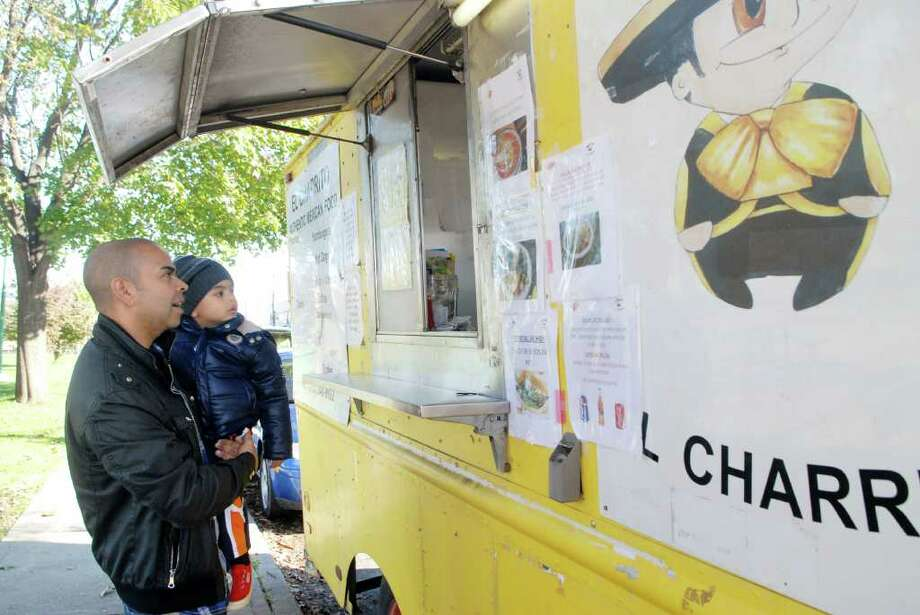 Carlos Menendez and son Mateo (2) place a order at the El Charrito food truck on Richmond Hill Ave in Stamford, Conn. on Tuesday November 1, 2011. Photo: Dru Nadler / Stamford Advocate Freelance