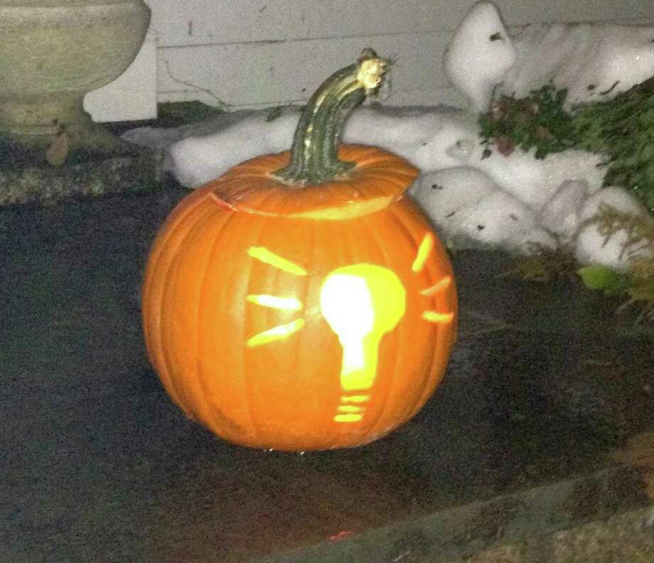 A carved pumpkin on a front stoop in Darien gives a nod to the recent power outages. Photo: Contributed Photo
