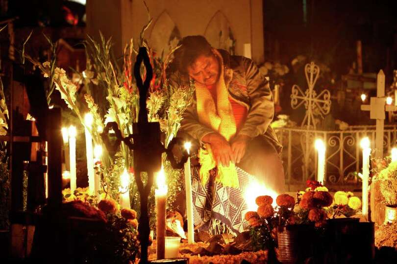 A man rests at the grave site of a departed loved one at the San Gregorio cemetery during the Dia de