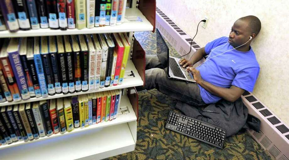 George Benibo, 27, takes refuge at the Danbury Public Library Tuesday. The Danbury resident has been out of power since Saturday afternoon around 4 p.m. Photo taken Tuesday, Nov. 1, 2011. Photo: Carol Kaliff