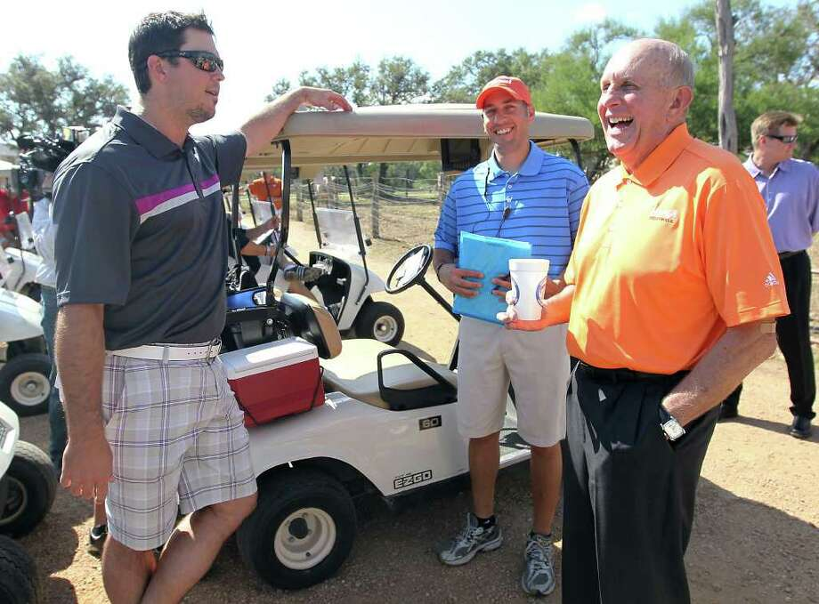 UTSA football head coach Larry Coker (right) shares a laugh with Boston Red Sox pitcher Josh Beckett (left) and Kids Sports Network CEO Brandon Parrott (second from right) prior to the start of the 2011 Matt Bonner Charity Golf Tournament for Kids Sports Network at Canyon Springs Golf Club on Tuesday, Nov. 1, 2011. Bonner, who is also the vice president of the NBA Players Association and on break from the contentious negotiations, appeared at the tournament and took time to meet with golfers who donated to the 13th annual charity tournament which benefits youth athletics. Photo: Kin Man Hui, SAN ANTONIO EXPRESS-NEWS / San Antonio Express-News