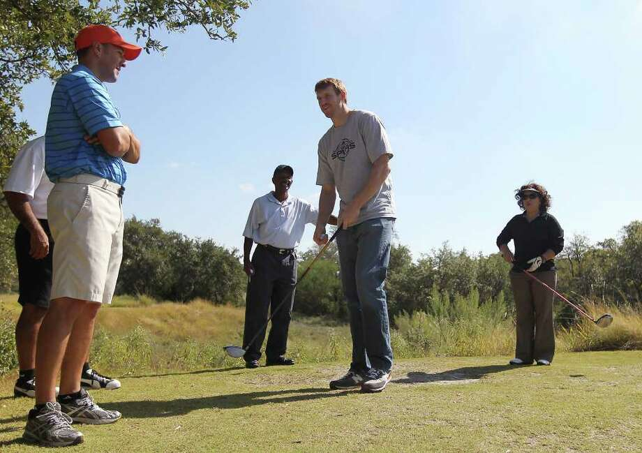Spurs forward Matt Bonner (center) chats with Kids Sports Network CEO Brandon Parrott (left) before taking a swing on the tee box as he hosts the 2011 Matt Bonner Charity Golf Tournament for Kids Sports Network at Canyon Springs Golf Club on Tuesday, Nov. 1, 2011. Bonner, who is also the vice president of the NBA Players Association and on break from the contentious negotiations, took time to meet with golfers who donated to the 13th annual charity tournament which benefits youth athletics. Photo: Kin Man Hui, SAN ANTONIO EXPRESS-NEWS / San Antonio Express-News