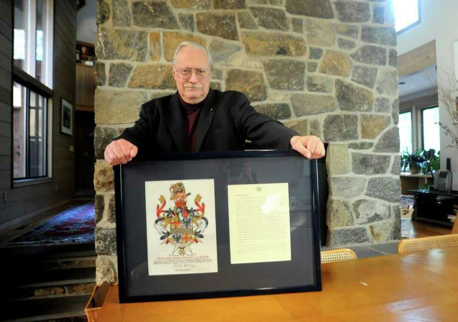 Peter von Braun, a Republican candidate for Board of Education displays material Tuesday, Nov. 1, 2011, shows he received an honorary knighthood from Queen Elizabeth II. Photo: Helen Neafsey / Greenwich Time