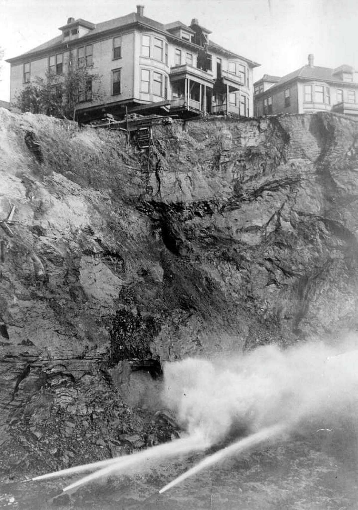 Water jets slice away part of old Denny Hill at the foot of Blanchard Street in 1908. Until it was flattened by city engineers, Denny Hill was a steep and inconvenient bump just north of downtown Seattle. When a homeowner wouldn't sell their property to the city, developers dug out the hill around them.