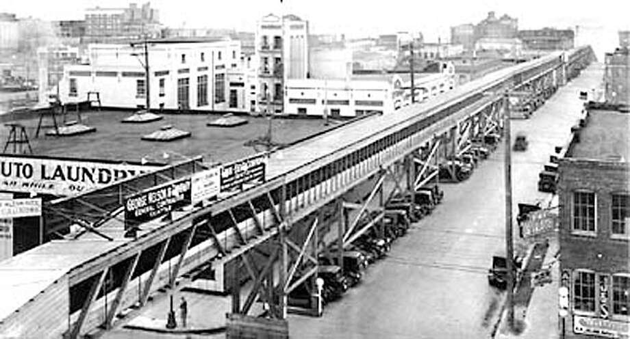An overhead wooden gallery was built along Battery Street to support a conveyor belt carrying dirt from the regrade project toward Elliott Bay. The gallery was torn down after the project's completion. Photo: Seattlepi.com File / Seattle Post-Intelligencer