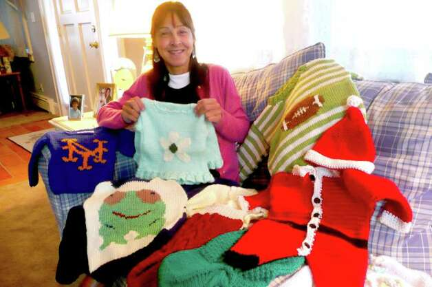 Master knitter Donna Stampien displays some of the many items she makes for the Greenwich Women's Exchange - including a Santa Claus suit made for an infant. Photo: Anne W. Semmes