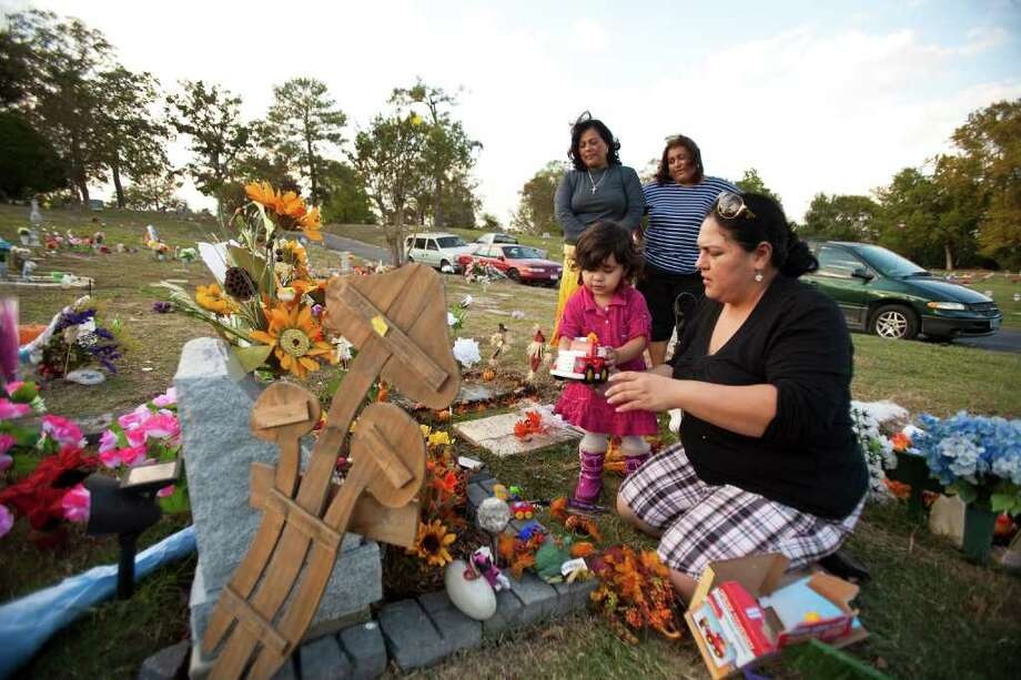 Sayra Huerta gives a toy train to her daughter Yvanna Rivera, 2, to decorate Sayra's nephew Santiago Huerta, who died as an infant, in observance of Dia de los Angelitos, Tuesday, Nov. 1, 2011, at the Hollywood Cemetery in Houston. November first is Día de los Angelitos, honoring deceased children and infants. Día de los Muertos, on November second, honors deceased adults and older teenagers. Photo: Nick De La Torre, Houston Chronicle / © 2011  Houston Chronicle