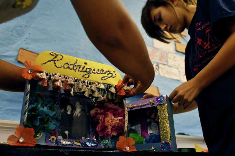 Laura Garza, left, puts the finishing touches on the altar she made with her daughter for her mother