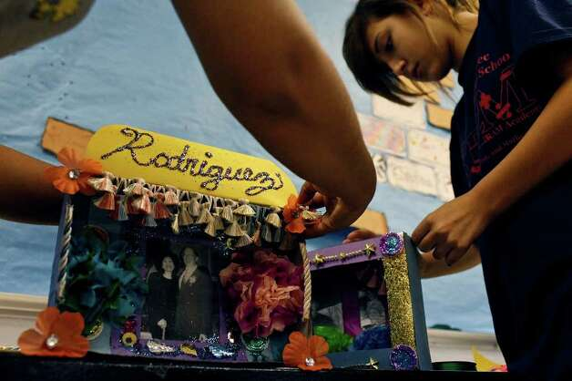 metro -  Laura Garza, left, puts the finishing touches on the altar she made with her daughter for her mother while Gabrielle Serna, 13, right, makes an altar for her cousin and grandfather for Wednesday's Dia de los Muertos celebration at Nimitz Middle School as part of parent night to involve parents in the school community on Tuesday, Nov. 1, 2011. LISA KRANTZ/lkrantz@express-news.net Photo: LISA KRANTZ, SAN ANTONIO EXPRESS-NEWS / lkrantz@express-news