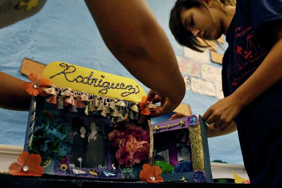 Laura Garza, left, puts the finishing touches on the altar she made with her daughter for her mother while Gabrielle Serna, 13, right, makes an altar for her cousin and grandfather for Wednesday's Dia de los Muertos celebration at Nimitz Middle School as part of parent night to involve parents in the school community on Tuesday, Nov. 1, 2011. LISA KRANTZ/lkrantz@express-news.net Photo: LISA KRANTZ, SAN ANTONIO EXPRESS-NEWS / lkrantz@express-news