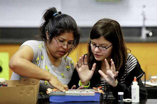 metro -  Anika Garza, 11, makes an altar with her mother, Laura Garza, for Wednesday's Dia de los Muertos celebration at Nimitz Middle School as part of parent night to involve parents in the school community on Tuesday, Nov. 1, 2011. The Garza's made their altar for Laura's mother, who passed away in 1997 from stomach cancer. LISA KRANTZ/lkrantz@express-news.net Photo: LISA KRANTZ, SAN ANTONIO EXPRESS-NEWS / lkrantz@express-news