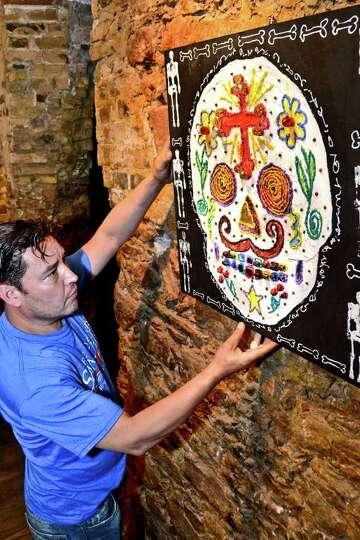Aldo Marc Ortegon arranges an illustration setup on the wall as a decoration for Dia De Los Muertos,