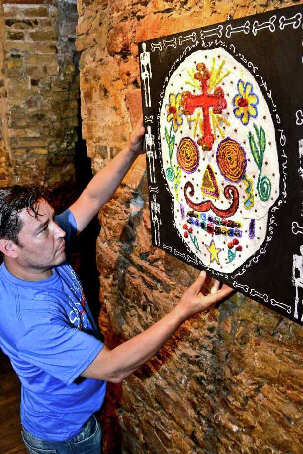 Aldo Marc Ortegon arranges an illustration setup on the wall as a decoration for Dia De Los Muertos, Tuesday evening at 201 Gallery. Photo: Danny Zaragoza / LAREDO MORNING TIMES