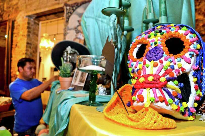 A fake decorated skull sits on an alter as Aldo Marc Ortegon arranges the other curios on the alter