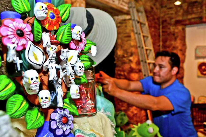 Aldo Marc Ortegon arranges the curios on an alter setup for Dia De Los Muertos, Tuesday evening at 2
