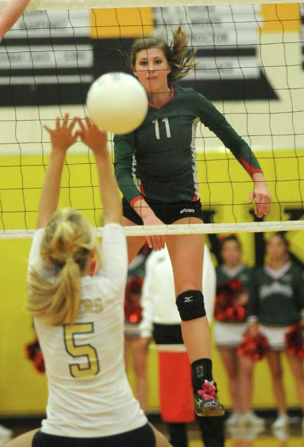 The Woodlands senior outside hitter Emily Phillips (#11) sends a kill past Klein Collins senior defensive specialist Meghan Molitor (#5) during their bi-district playoff match on Tuesday at Klein Oak High School. Freelance photo by Jerry Baker Photo: Jerry Baker, For The Chronicle