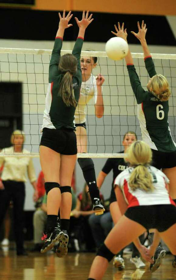 Klein Collins senior middle blocker Molly McCage, center, goes for a kill between  The Woodlands senior outside hitter Emily Phillips, left, and sophomore middle blocker Lexi Schnakenburg (6). Photo: Jerry Baker, For The Chronicle