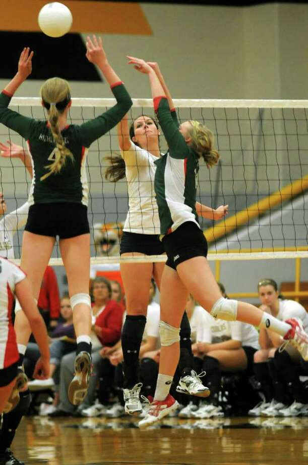 Klein Collins senior outside hitter Heidi Otto, center, goes to the net against The Woodlands junior middle blocker Maddie Slater, left, and senior setter Kate DeLess. Photo: Jerry Baker, For The Chronicle