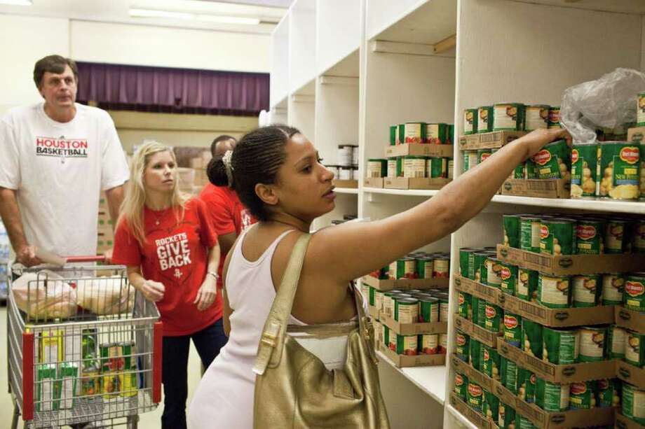 CAN REACH THE TOP SHELF: Rockets coach Kevin McHale, left, helps out Tuesday at Target Hunger, an organization that helps distribute food to Houston families. Photo: Eric Kayne / © 2011 Eric Kayne