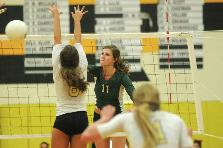 The Woodlands' Emily Phillips (11) sends one of her 19 kills past Klein Collins' Amy South. Photo: Jerry Baker