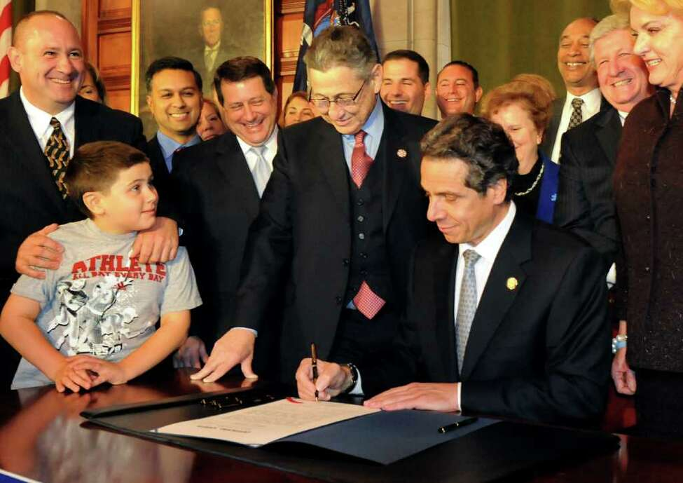 Gov. Andrew Cuomo, right, signs a bill to give autistic patients access to covered medical care on Tuesday, Nov. 1, 2011, at the Capitol in Albany, N.Y. Alexander Smith, 10, who has autism, left, and his father, Michael, chairman of the Foundation for Autism Information and Research Inc., are on hand for the signing. (Cindy Schultz / Times Union)