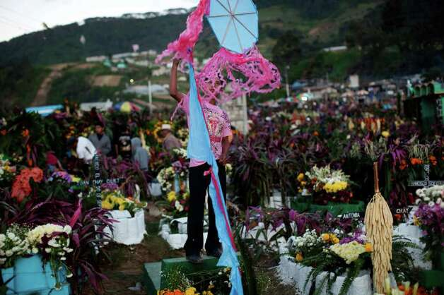 A boy flies a kite in the cemetery on Day of the Dead in Zunil, Guatemala, Tuesday Nov. 1, 2011.  Because Mayans believe the dead are allowed to visit their families on earth for one day, family members fly kites to guide their departed relatives to their earthly homes.  Also decorating graves with fresh flowers is common throughout Latin America, as is having a picnic at the departed relative's grave site. Photo: AP