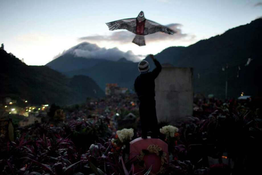 A boy flies a kite in the cemetery on Day of the Dead in Zunil, Guatemala, Tuesday Nov. 1, 2011. Photo: AP