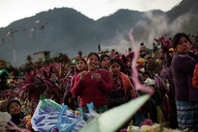 People laugh as they fly kites by the graves of their relatives on Day of the Dead in Zunil, Guatema