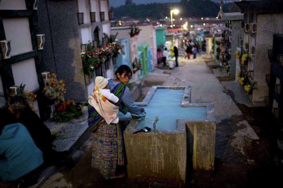 A woman fills a jug with water for the flowers she is using to decorate the graves of relatives on the eve of Day of the Dead celebrations in Salcaja, Guatemala, Monday Oct. 31, 2011. Photo: AP