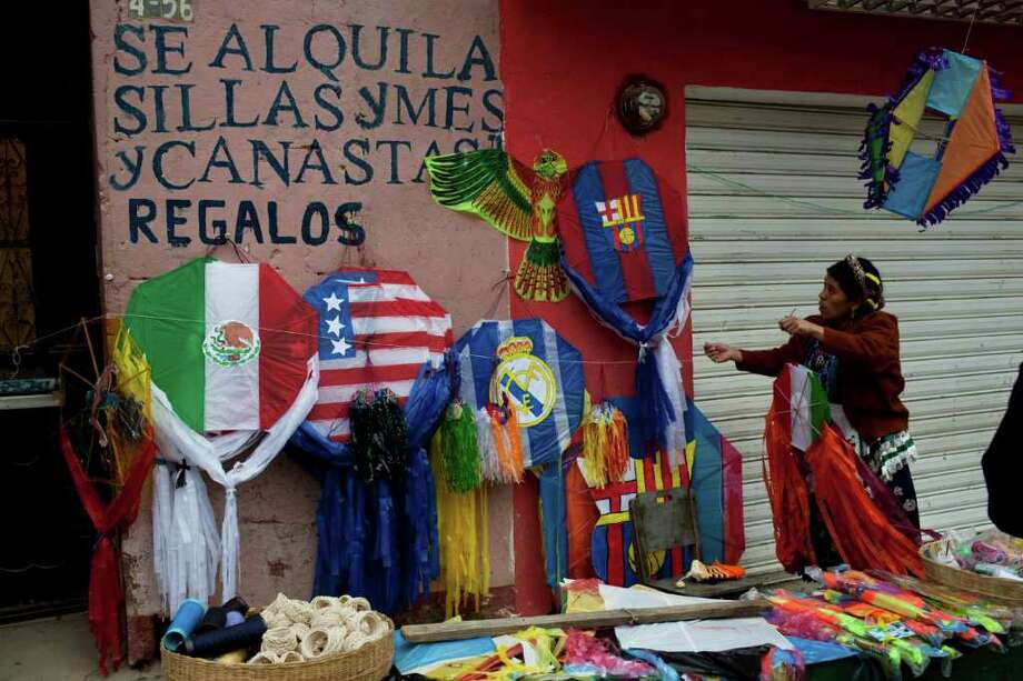 A street vendor arranges her kites for sale near the local cemetery during the Day of the Dead celebrations in Almolonga, Guatemala,Tuesday Nov. 1, 2011.  Photo: AP